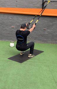 Damien performing a squat using the suspension trainer
