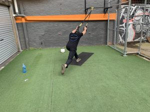 Damien performing a single leg dead lift using a suspension trainer
