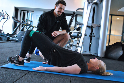 client performing banded glute bridge exercise