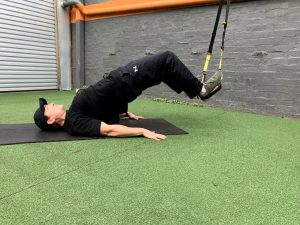 Damien performing a Glute/hamstring bridge using a suspension trainer