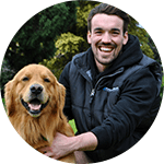 ryan bartlett trainer kneeling with his dog smiling