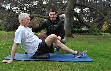 retired client with personal trainer in park